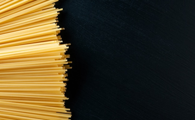 Желтые сырые макароны спагетти на черном фоне бетона