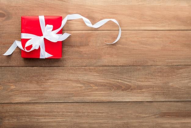 Подарок в красной упаковке на деревянном фоне