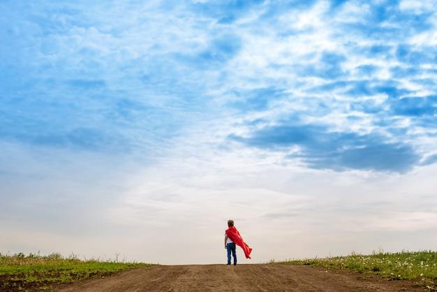 Маленький дошкольник, играет супергероя на улице