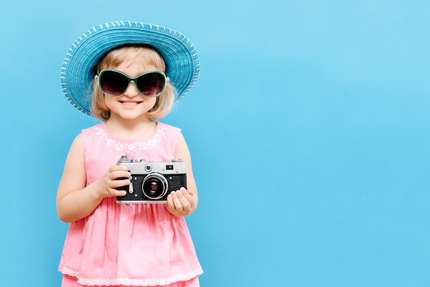 Маленькая девочка с камерой в руке в студии