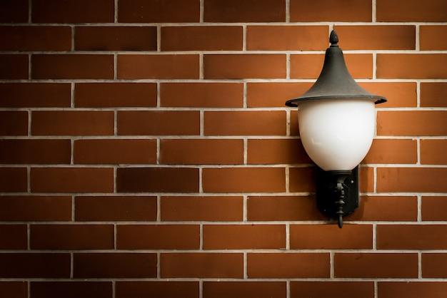 茶色のレンガの壁と古いランプ。ビンテージフィルター付き