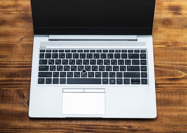 Ноутбук с кириллицей на деревянной поверхности