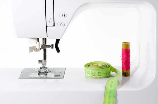 Электрическая швейная машина с аксессуарами на белом фоне