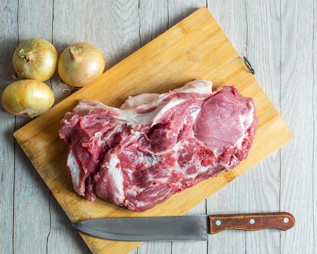 生肉、タマネギ、木の板に古いナイフ