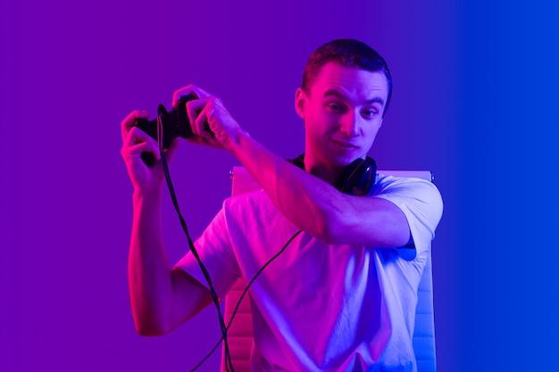 Портрет веселого счастливого юнца с геймпадом в руках с энтузиазмом играет в видеоигры