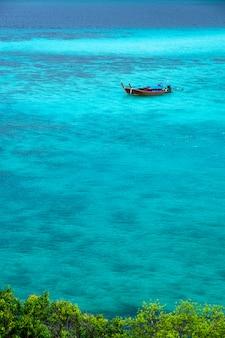 水中のサンゴ礁を見下ろす澄んだエメラルドグリーンの海にボートが浮かんでいます。