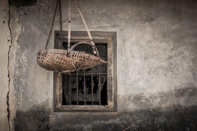 Плетеная корзина из бамбука висит на окнах китайского дома