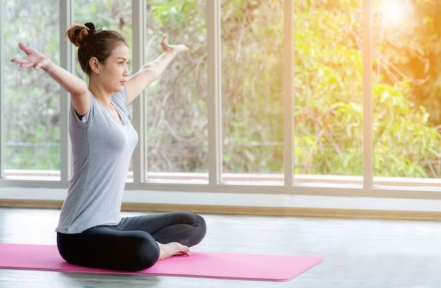 ヨガ、エクササイズ、窓の姿勢、ロフトスタジオ、白いリラクゼーションエクササイズまたはヨガのクラスを練習しているアジアの女性