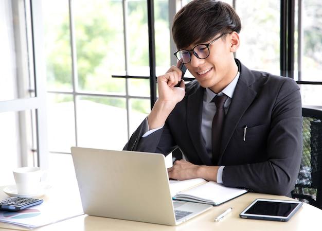 Портрет улыбающегося молодого бизнесмена, говорить на своем смартфоне, в то время как он работает на своем компьютере, сидя в своем офисе на столе, одетый в черный костюм.