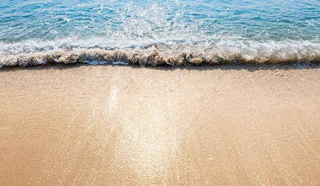 青い海の波日光反射砂のビーチの背景