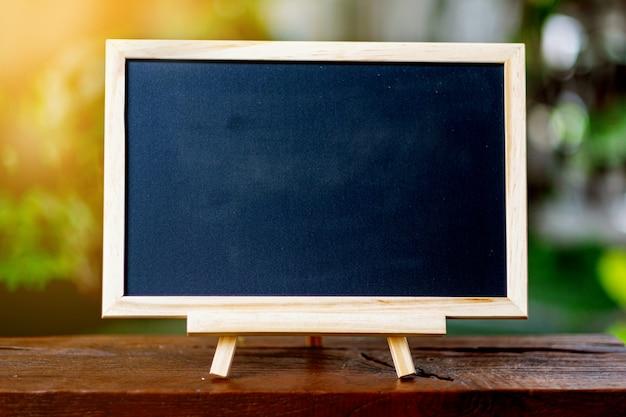 木製のテーブルの上に置かれた小さな黒板後ろは緑の木です。教育イラスト用