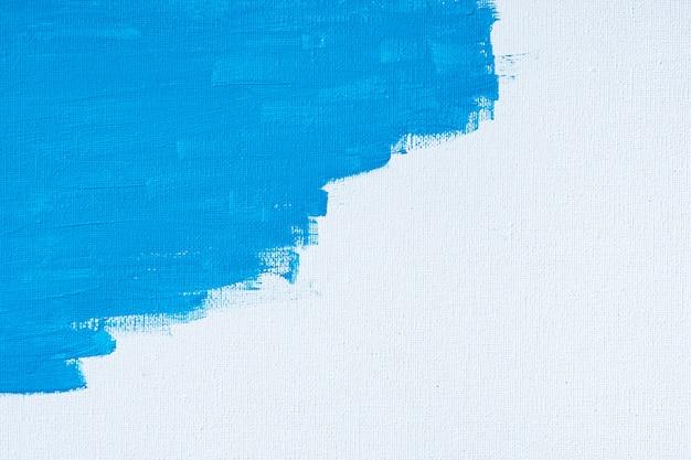 青い色の抽象的なペイントブラシと白いキャンバスの背景に線を描画する水の色油色のテクスチャ