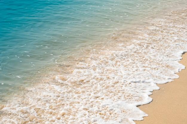 砂浜で青い海の波。
