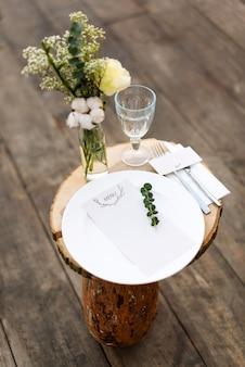 夕食の準備ができて装飾されたテーブルの紙メニュー。屋外の結婚式やレストランでの別のイベントのために、花、皿、飾り付きの美しい装飾が施されたテーブル。