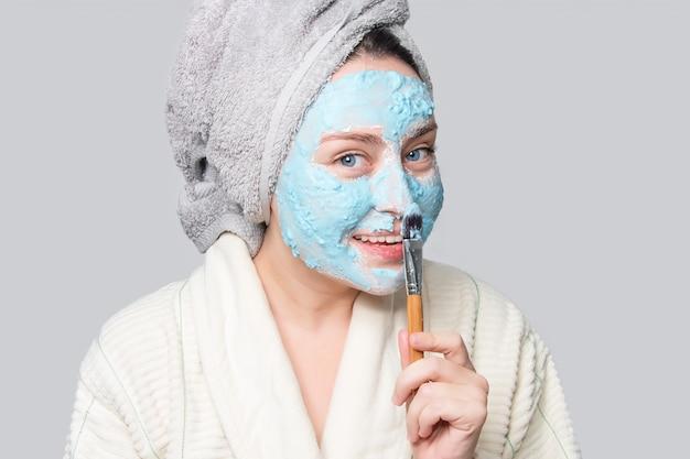 Женщина прикладывая лицевую маску глины на салоне курорта или дома, тема ухода за кожей. маска для лица, спа-салон красоты с копией пространства
