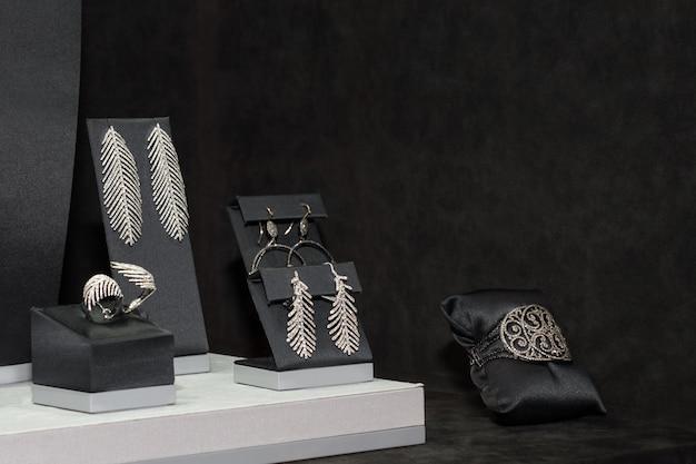 Разнообразие ювелирных изделий в витрине. кольца, браслеты, серьги и колье на подставках для продажи.