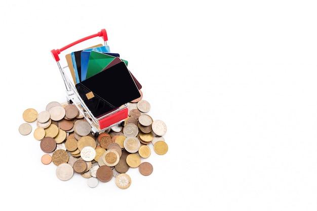 クレジットカードでのショッピングカートは、白い背景の上のコインの山に乗っています。クレジットカードが勝ち、現金は負けました。新旧の支払い方法。