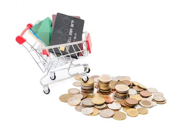 クレジットカードでのショッピングカートは、白い背景の上のコインの山に乗っています。
