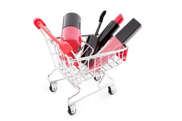 手押し車が白い背景で隔離のメイク。赤い口紅、マスカラ、ピンクのリップグロス、パウダー、マニキュア。ショッピングカート、割引または販売をテーマにした化粧品。必需品と美しさのお気に入り