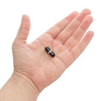 手持ちまたは黒のカプセルを提供しています。白い背景で隔離されました。手のひらの薬、薬または医師の処方箋。