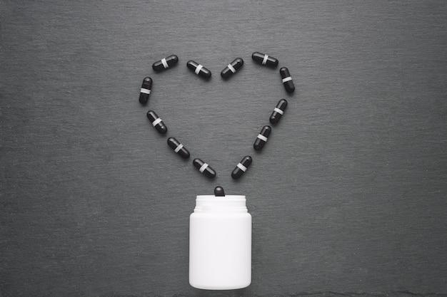 ハート型に配置された黒のサプリメントカプセルは、白いボトルから注がれます。平面図、フラットレイアウト、コピースペース。医学のテーマ、医療コンセプト。