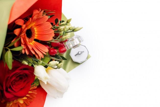 Обручальное кольцо в подарочной коробке с ярким букетом цветов. предложение жениться. подарок на день святого валентина. брачное предложение для любимой женщины. символ любви и брака.