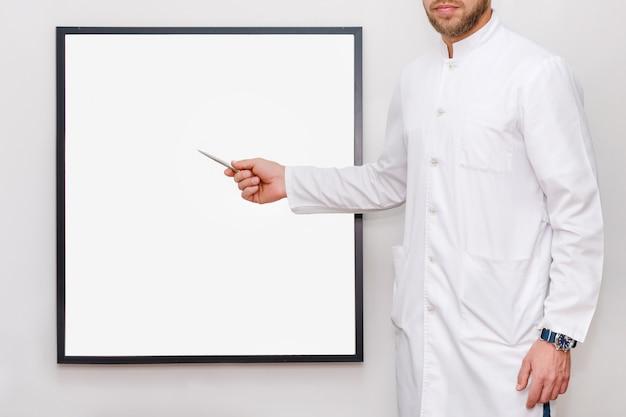 額縁やモックアップのためのポスターを指している白い制服を着た男。空のフレーム、医学、ビジネス、広告コンセプト-白い空白板を持つ男を示す医師やシェフ