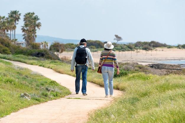 Путешествия и туризм. пожилая семейная пара, наслаждаясь видом вместе ходить вдоль берега моря, вид сзади