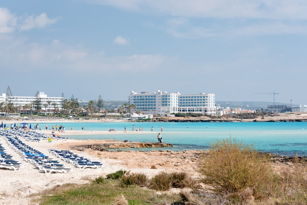 Зонтики и шезлонги на пляже. пластиковые лежаки возле моря. тропический отдых, летний фон.