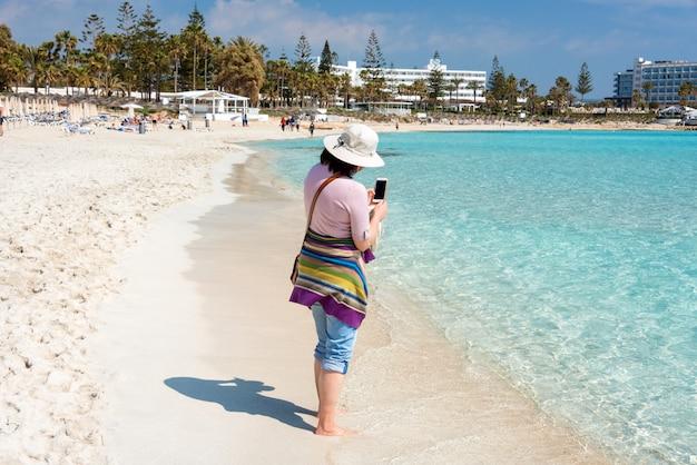 スマートフォンで海の写真を撮るビーチで帽子の裸足の女。夏の休日、休暇、旅行、人々の概念