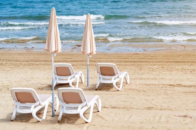 Зонтики и шезлонги на пляже. пустые пластиковые лежаки возле моря. тропический отдых, летний фон.