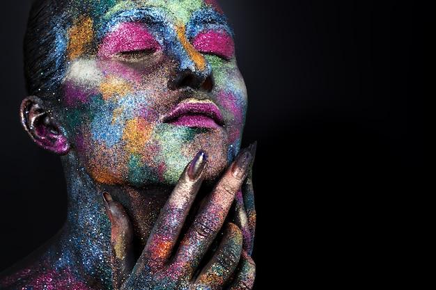 Молодая художническая женщина в черной краске и красочном порошке. светящийся темный макияж. творческий боди-арт на тему космоса и звезд. бодиарт проект: искусство, красота, мода.