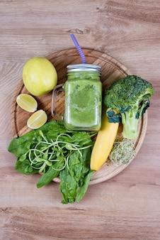 新鮮な緑の野菜と緑の瓶にスムージー。デトックス、ダイエットや健康食品のコンセプトです。ブロッコリー、ほうれん草、マイクログリーン、ライム、バナナの木製のテーブルとの食事の飲み物の石工の瓶。上面図。