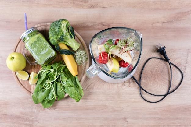 ブロッコリー、ほうれん草、マイクログリーン、ライム、バナナ、木製のテーブルの食材を使ったミキサーと食事の飲み物の石工の瓶。上面図。デトックス、ダイエットや健康食品のコンセプトです。