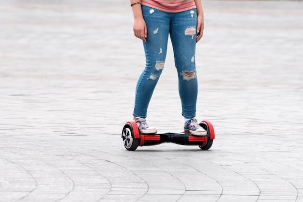 Молодая женщина верхом на ховерборде на городской площади. новые движения и транспортные технологии. закройте вверх собственной личности двойного колеса балансируя электрический скейтборд. люди на электрических скутерах на открытом воздухе.