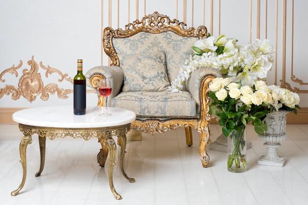 Роскошный винтажный интерьер в аристократическом стиле с элегантным креслом и цветами. бутылка и бокал вина на столе. ретро, классика.
