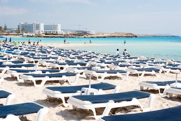 Зонтики и шезлонги на пляже. пластиковые лежаки возле моря.