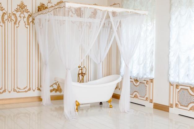 Роскошная ванная комната в светлых тонах с золотыми деталями мебели и навесом. элегантный классический интерьер.