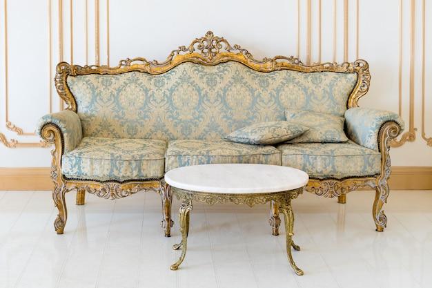 Роскошная гостиная в светлых тонах с золотыми деталями мебели. элегантный классический интерьер