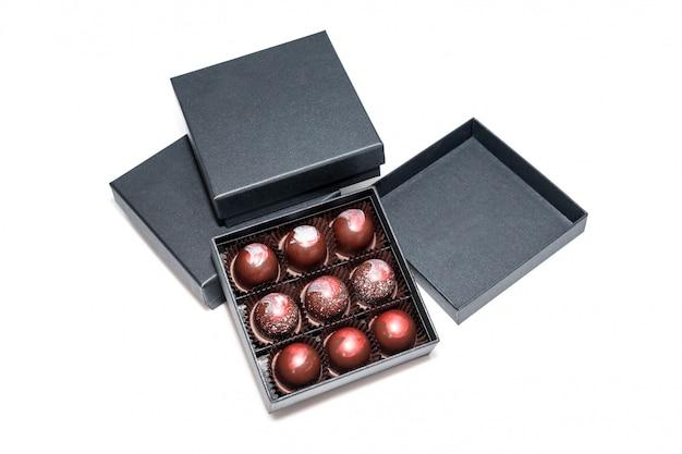 白い表面に分離されたギフトボックスのチョコレート菓子。ギフトボックスに入ったチョコレート菓子の詰め合わせ。カラフルなチョコレートボンボンのセットです。