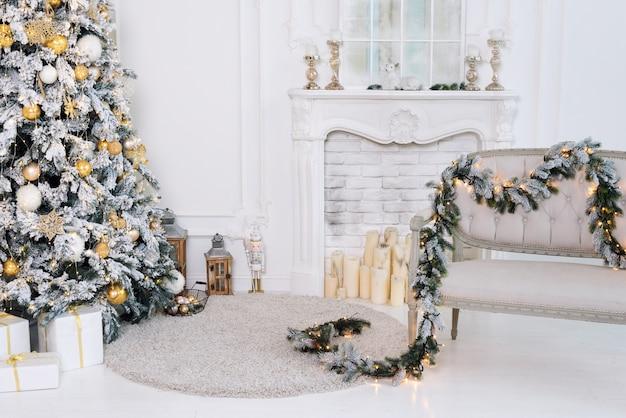 暖炉とソファのある豪華な白いクラシックインテリアの美しい装飾が施されたゴールデンクリスマスツリー。