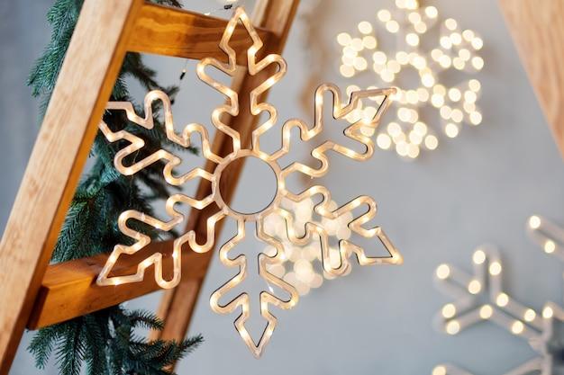 Снежинки сделаны из гирлянды огней на сером деревенском с деревянной лестницей. рождественские украшения