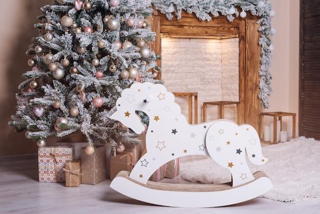 美しい休日の装飾が施された部屋のクリスマスツリー、木製の馬、暖炉のそばのプレゼント。