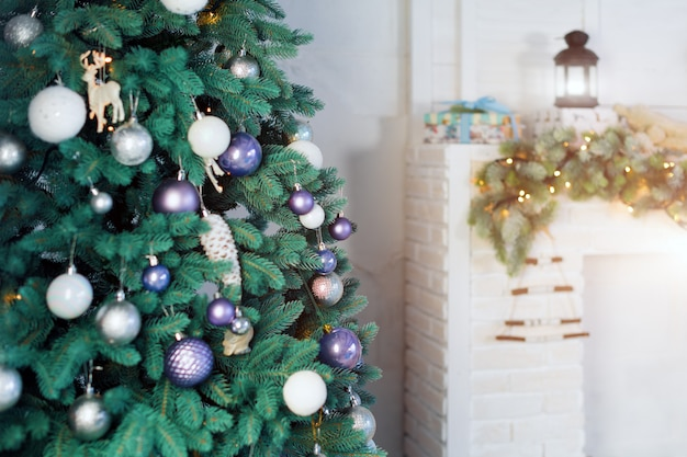 暖炉のそばのクリスマスツリーが飾られた美しい休日の部屋。