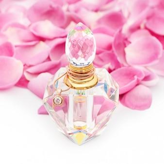 花びらの中でネックレスの香水瓶。香水、化粧品、フレグランスコレクション