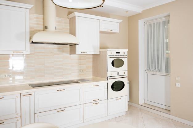 豪華な家のモダンで明るく、きれいなキッチンインテリア。クラシックまたはヴィンテージの要素を備えたインテリアデザイン。実用的で設備の整ったキッチン。
