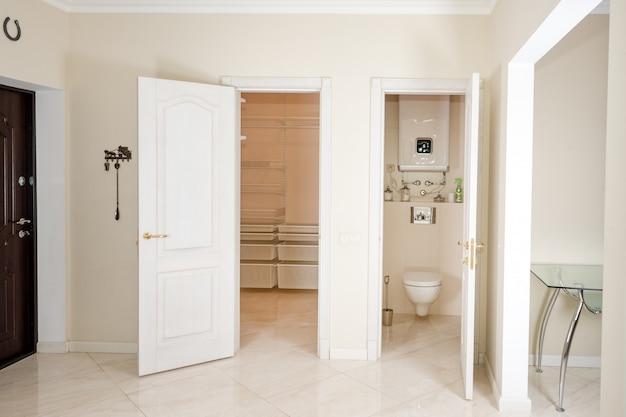 家のインテリア。ウォークインクローゼットとトイレへの白いドアが付いている入口の廊下。