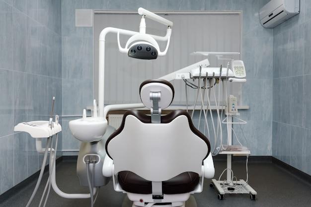 歯科医のオフィス。現代の歯科用キャビネット。現代のクリニックの歯科用器具とツール、歯科矯正医による使用を待っている専門の歯科用椅子