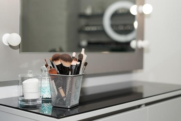 プロの化粧ブラシは、サロンミラーの近くにクローズアップを設定します。ぼかしの背景にプロのメイクアップアーティスト用の任意のサイズのブラシ