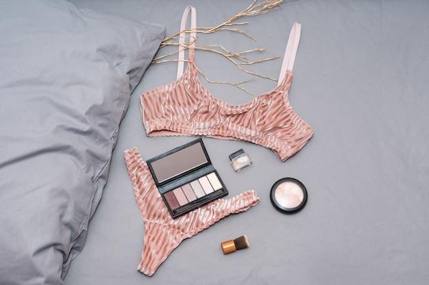 Комплект гламурного стильного сексуального кружевного белья с женскими аксессуарами на серых простынях